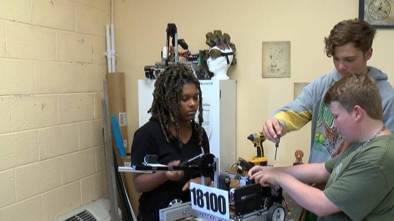 Three robotics program members are taking a look at one of their robots