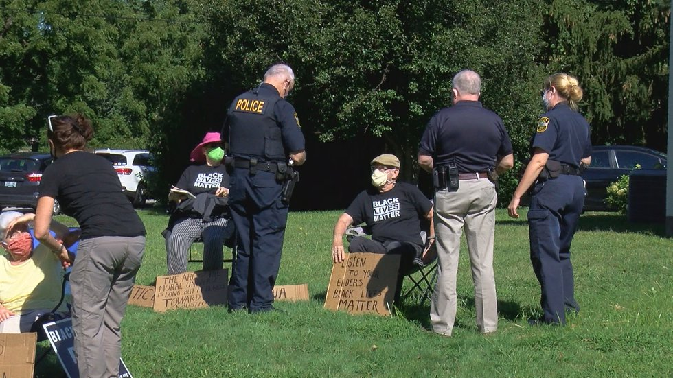 Louisville Metro police talk with a group of senior citizens who sat on the front lawn of...