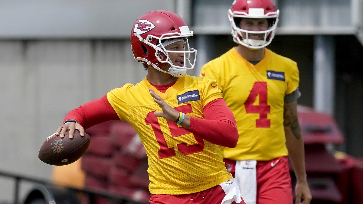 Kansas City Chiefs quarterback Patrick Mahomes (15) throws while teammate Chad Henne waits his...