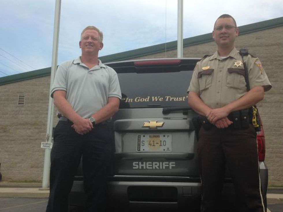 Todd Ham, L, who donated the stickers, stands next to squad car with Sheriff Travis Allen