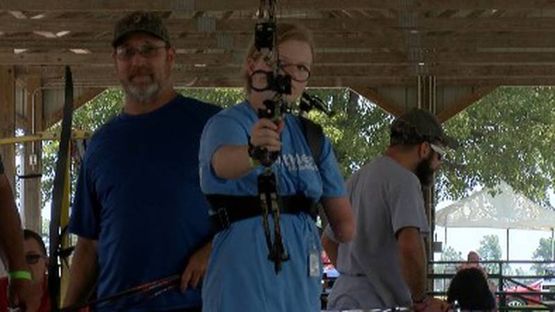 A NubAbility camper with limb loss shoots a bow in an archery session.