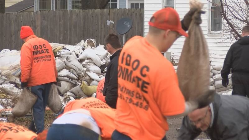 A work team with the Illinois Department of Corrections is starting to remove sandbags that...