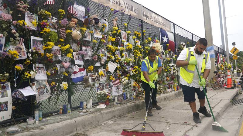 Workers with Surfside Public Works sweep up dead flowers from a makeshift memorial for victims...