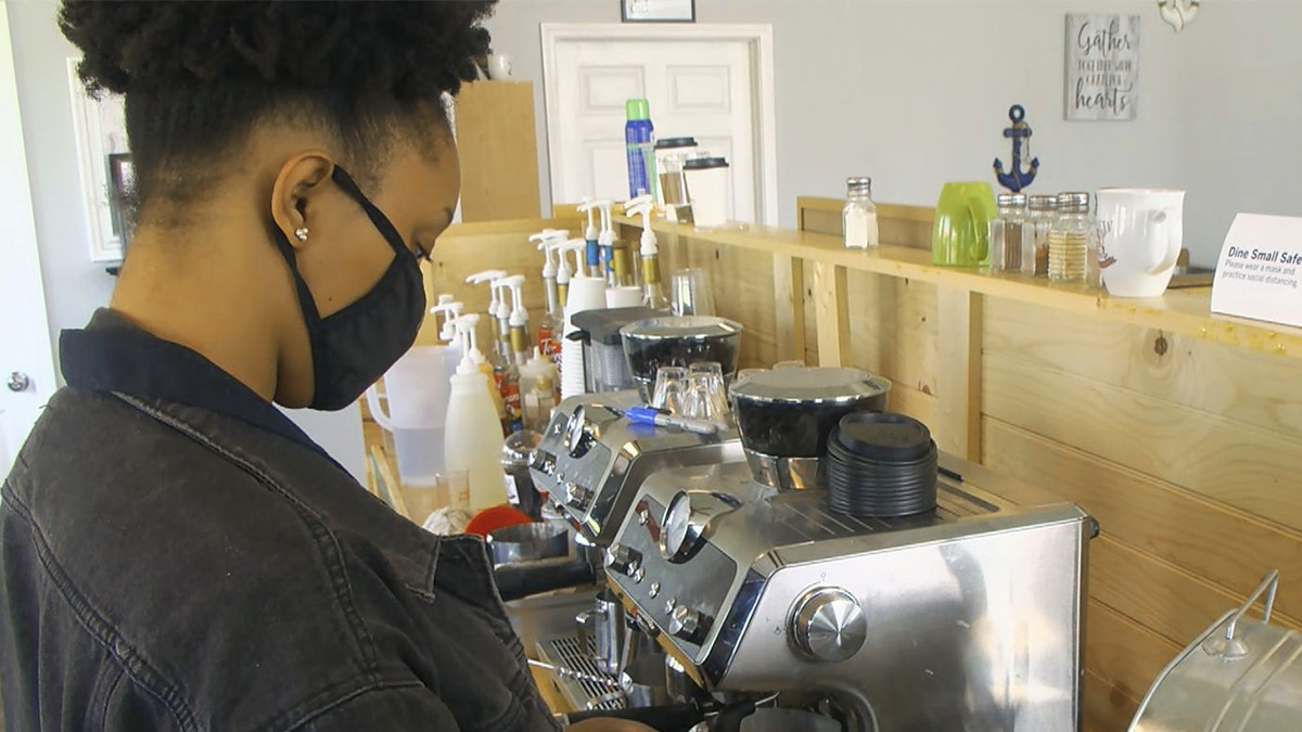 A barista at Brew and Sip Coffee Bar in Louisville, KY wearing a face mask