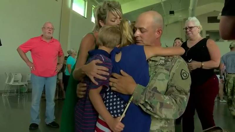 A family hugs before the second group of soldiers is deployed Friday from Owensboro