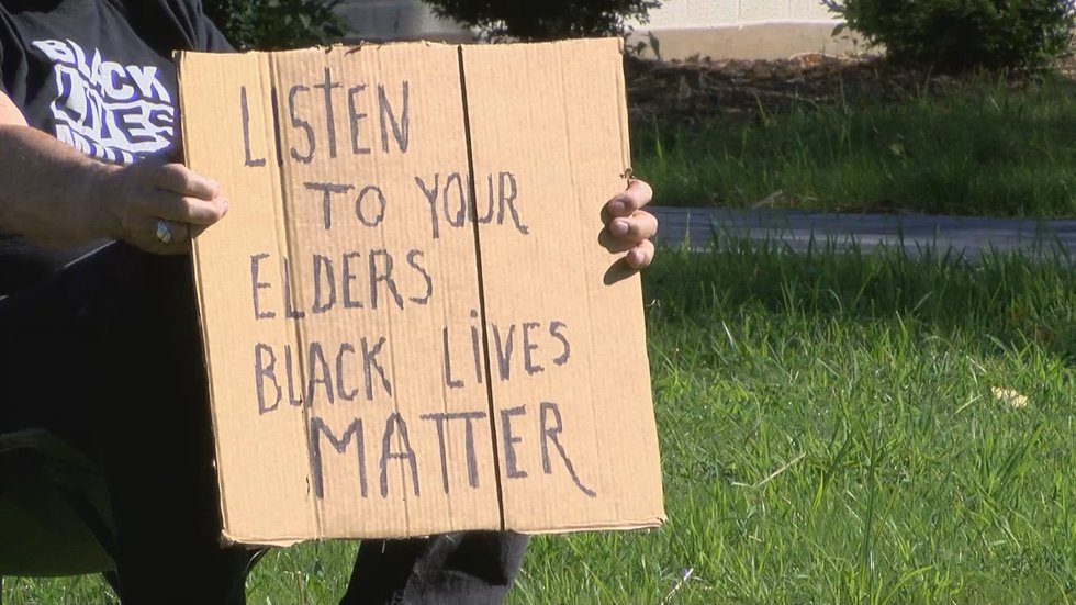 One of the protesters from to Standing Up For Racial Justice, or SURJ, held a sign calling for...