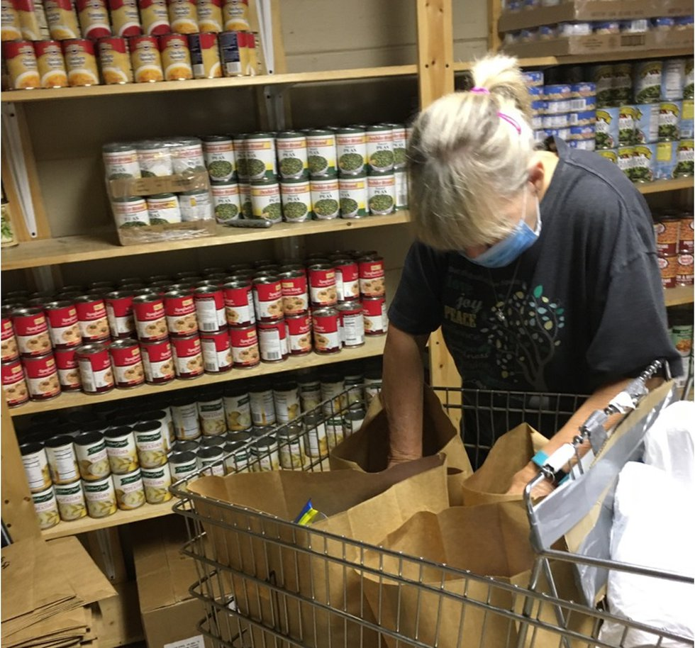 Lighthouse Community Food Bank volunteer Beverly Conner loads groceries into sacks to...