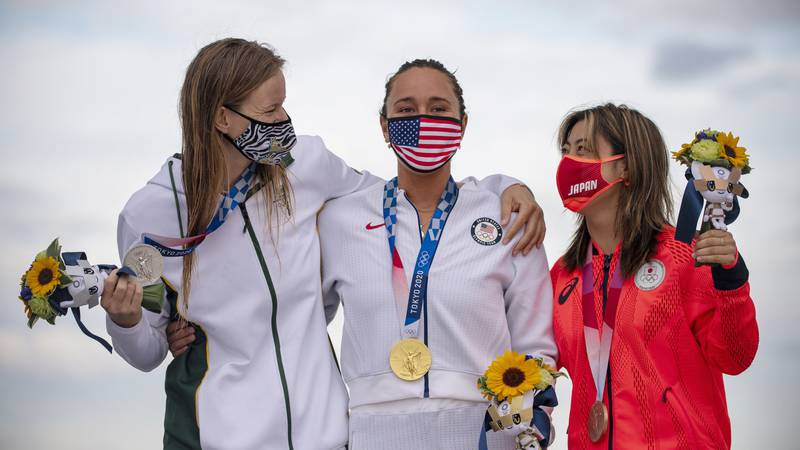 Carissa Moore, center, of the United States, wearing her gold medal, South Africa's Bianca...