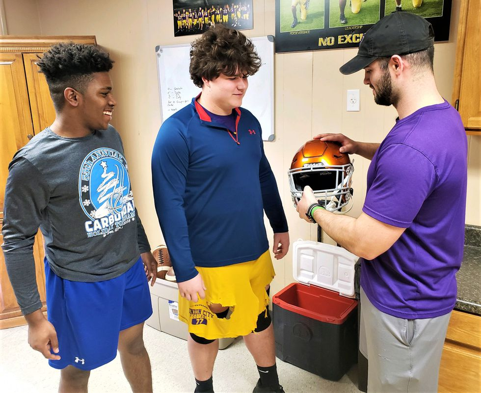 Golden Tornadoes football players were fitted for new and safer helmets.  (Source: Union City...