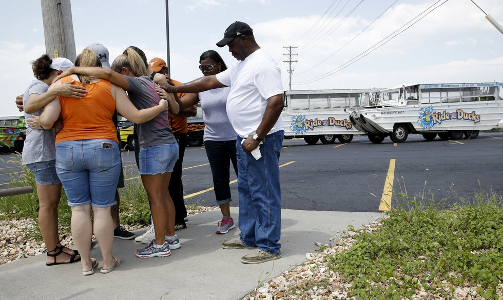 People pray outside Ride the Ducks, an amphibious tour operator involved in a boating accident...