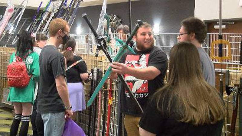 A person shows displays two swords at the Cape Anime Con 2021 event.